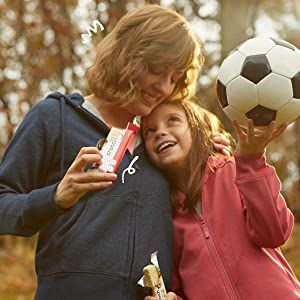 Woman hugging young girl holding a soccer ball both eating power crunch bars