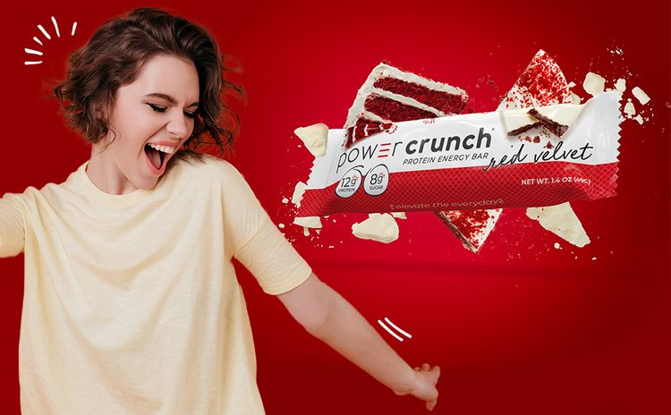 woman smiling and dancing next to power crunch red velvet bar